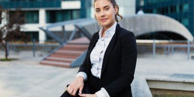 Beautiful businesswoman holding notebook in business district